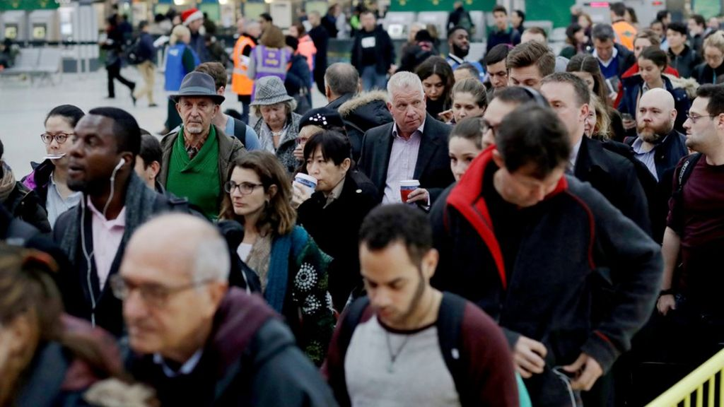 Passengers at London Victoria queue for an express train to Gatwick Airport