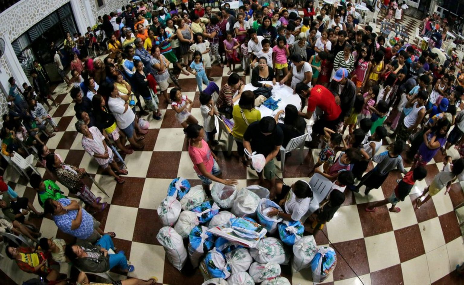 People gather at a gymnasium turned into an evacuation centre for the distribution of relief goods in San Jose city, Nueva Ecija province.