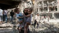 A Syrian man carries two girls as he walks across rubble in the northern city of Aleppo - 17 September 2015