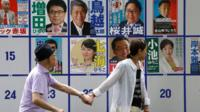 People walk past election posters in Tokyo. Photo: 31 July 2016