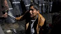A disabled protester confronts police blocking him from reaching the National Palace, where President Evo Morales has his offices