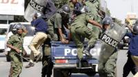 Zambian police officers arrive at the University of Zambia where students protest against the government's removal of fuel and mealie meal subsidies on May 17, 2013 in Lusaka