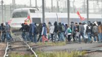People cross railway lines during a protest against labour law reforms in Rennes, on May 26, 2016