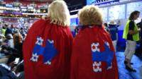 Supporters of Hillary Clinton with capes featuring her logo