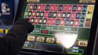 A hand presses the screen of a fixed odds betting terminal