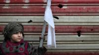 An Iraqi girl holding a white flag stands on a street with her mother as Iraqi security forces secure Mosul's Al-Dawasa neighbourhood on 13 March