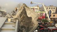Rescue personnel work on a damaged building after an earthquake in Tainan