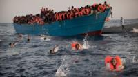 migrants from Eritrea jump into the water