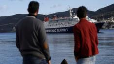 Migrants staying in temporary housing at the port of the eastern Greek island of Samos watch a departing ship
