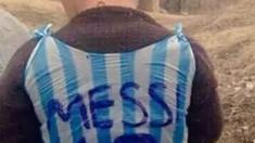 A boy wearing a Lionel Messi football shirt made out of a carrier bag