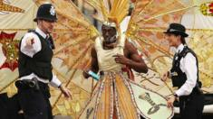 Police officers direct a carnival-goer at the Notting Hill Carnival 2012