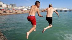 Two boys jump into the sea in brighton
