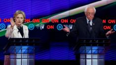 Democratic U.S. presidential candidate Hillary Clinton (L) speaks as Senator Bernie Sanders reacts during a Democratic debate hosted by CNN and New York One at the Brooklyn Navy Yard in New York April 14, 2016.