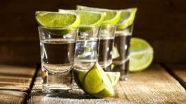 Shots of tequila with lime wedges