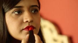 A young Pakistani woman puts on red lipstick