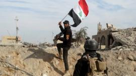 A member from the Iraqi security forces holds an Iraqi flag in the city of Ramadi