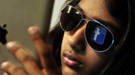 Young Indian woman browses Facebook on her tablet