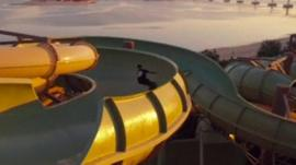 Three skateboarders have a go at skating some of the rides at a waterpark in Dubai while it is closed for cleaning.