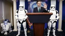 White House Press Secretary Josh Earnest appears in the briefing room with Star Wars Stormtroopers and Robot R2-D2