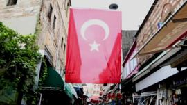 A flag flies above a street lined with shops