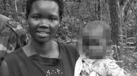Evelyn Amony holding her daughter, standing beside two male relatives in the LRA, in the Democratic Republic of Congo in 2006