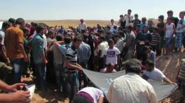Crowds at burial site for Alan Kurdi and his family