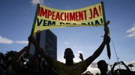 An anti-government protestor holds a sign that reads in Portuguese