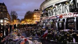 Flowers and candles continue to be put at Place de la Republique