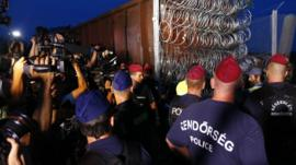 Hungarian police officers guard the area as a rail wagon prepared with barbwire arrives to seal the border fence between Serbia and Hungary in Roszke