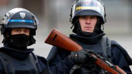 An armed policeman and a CRS riot policeman in Saint-Denis