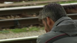 Migrant man sat next to empty railway lines