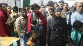 Migrants queue as they arrive in an emergency shelter at the Hungarian-Austrian border in Nickelsdorf, Austria