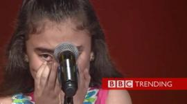 a girl crying in front of a microphone