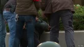 Police detain a man in the Molenbeek quarter of Brussels