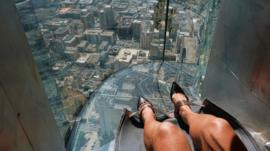 A rider at the top of a glass slide in Los Angeles