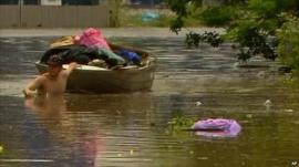 Man dragging boat of his possessions through flood water