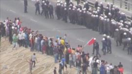 Protesters and police on a road in Manama