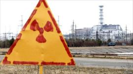 Radiation sign and damaged fourth reactor at the Chernobyl nuclear power plant