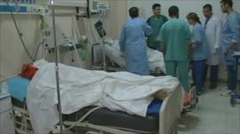 Hospital staff stand around patients bed in Misrata