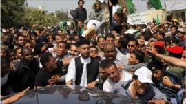 Saif al-Islam Gaddafi (c) in the crowd attending the funeral.