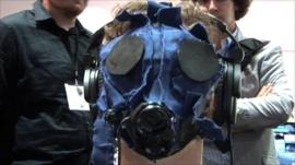 Video gamer wearing gas mask to become immersed in a video game that uses sound