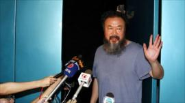 Ai Weiwei waves to the press from his studio but did not want to speak to the media