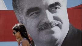 Woman walking past poster of assassinated PM Rafik Hariri