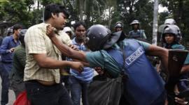 Bangladeshi policeman detains a protester in Dhaka