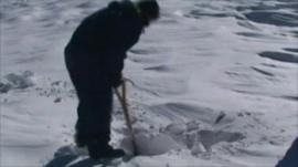 Rescue worker tries to dig through snow to reach stranded people
