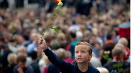 A boy holds up a rose at a memorial vigil in Norway