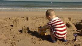 Little boy building sand castles on beach
