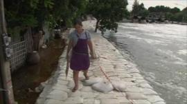 Woman walking along dam made of sandbags next to swollen river