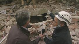 Tim Willcox and rescue worker look at collapsed building