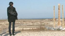 Woman at memorial for tsunami dead in Sendai, Japan